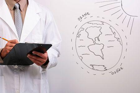 ozon: Mann in einem weißen Laborkittel aufschreiben von Informationen über die Ozon-Schicht.  Lizenzfreie Bilder