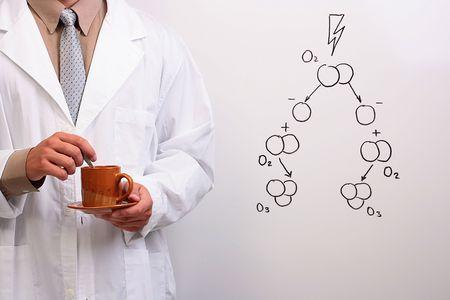 L'homme dans une blouse blanche tenant une tasse et une assiette � c�t� d'un dessin de la formation d'ozone.