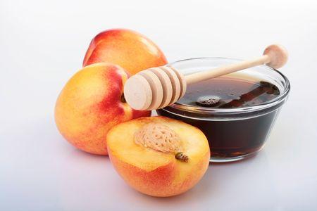 滑らかな桃、白い背景の上に蜂蜜。