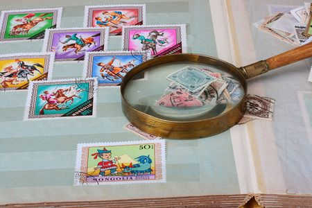 Collection of stamps in an album with magnifying glass. Imagens