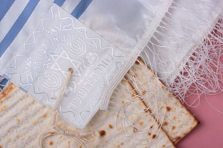 Two pieces of matzah laying next to a blue and white tallit. photo