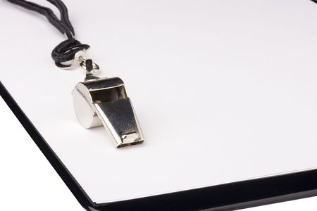 A silver whistle with a black string laying on a clipboard with white paper. Add your text to the background. photo