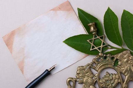 A menorah next to an old piece of paper. Add your text to the paper. photo