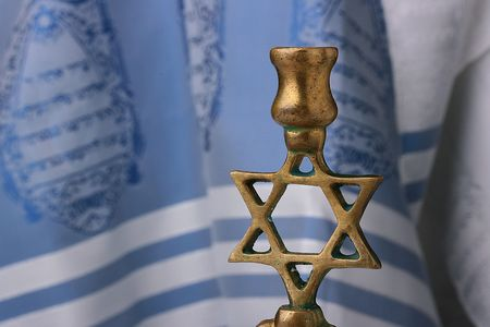 simchat torah: Menorah in front of a blue and white tallit. Add your text to the background.