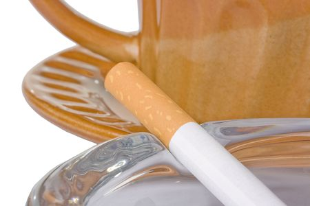 A filtered cigarette resting on an ashtray in front of a brown cup and plate.