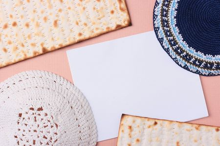 simchat torah: Blue and white kippahs laying next to matzah and a white piece of paper. Add your text to the paper.
