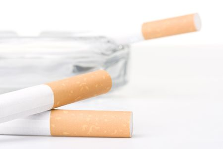Two filtered cigarettes laying in front of an ashtray.