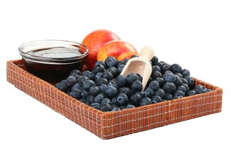 Peach, honey and blueberry in a wooden wattled tray.