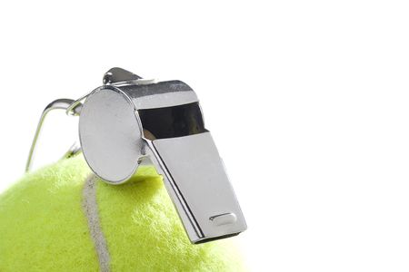 A silver whistle laying on a yellow tennis ball. Add your text to the background. photo