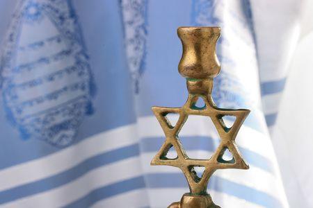 sukkot: Menorah davanti un tallit bianco e blu. Aggiungere del testo allo sfondo.