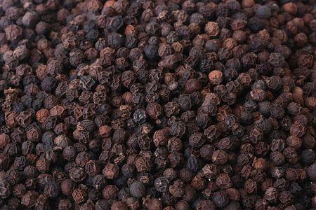 Spice - black dried pepper peas, a black background.