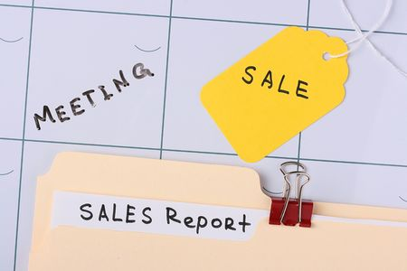 A manila sales report folder laying on a calendar next to a sale tag. Stock Photo - 7605484