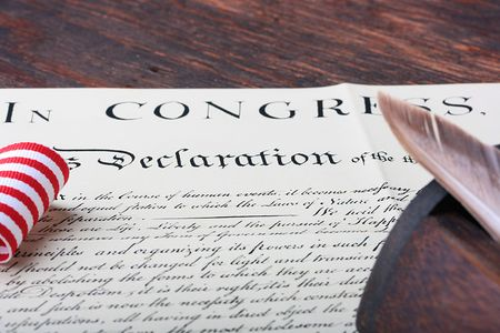 declaration: The ancient text of the declaration on independence of the United States of America with a casket and a feather for the write. Stock Photo