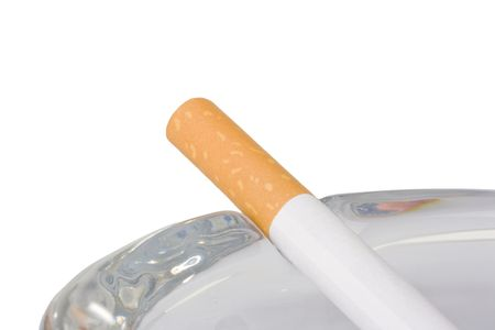 A filtered cigarette neatly placed on a glass ashtray.