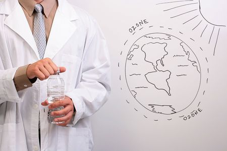 Man in a white lab coat opening a bottle of water while standing next to a drawing of the ozone layer.