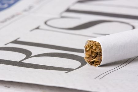 A cigarette laying on top of a newspaper with the word business on it.