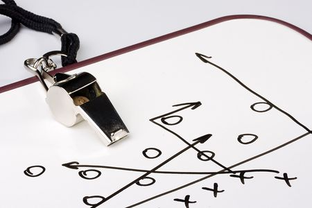A silver whistle next to a drawing of a football play. Stock Photo