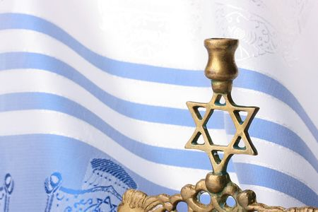 simchat torah: Menorah standing in front of a blue and white tallit. Add your text to the background. Stock Photo