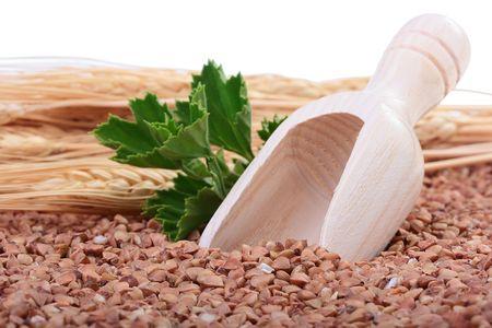 Buckwheat groats with a wooden deep spoon for packaging. Zdjęcie Seryjne