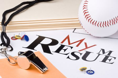 A silver whistle next to a baseball and a resume. photo