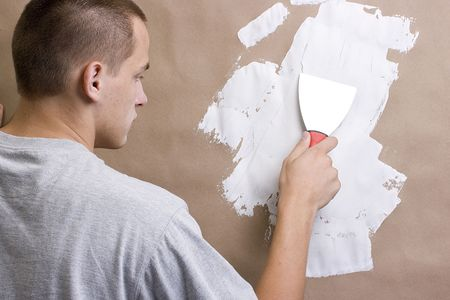 plastering: Caucasian man plastering a brown wall with a pallet. Stock Photo