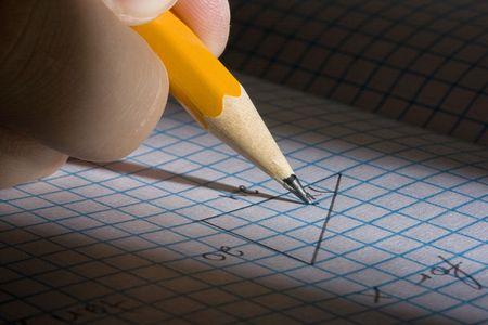 Student solving a math problem using a pencil. photo