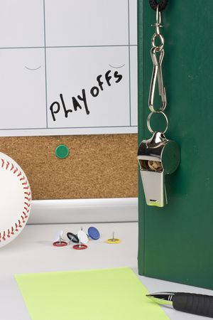 A silver whislte on a green notebook placed next to a baseball and a calendar with the playoffs date on it. photo