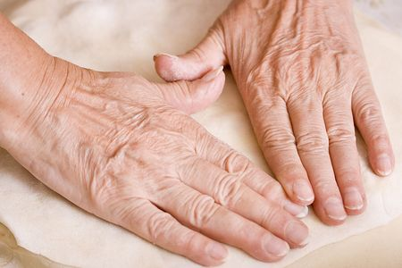 flattened: Hands of an old woman on flattened dough.