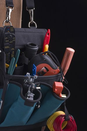 Electricians bag with tools on a black background. Stock Photo