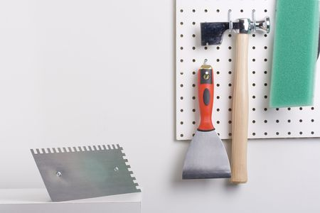 Tools used for wall plastering hanging on a pegboard.