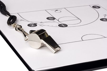game equipment: A silver whistle laying on a paper with the basketball game plan on it. Stock Photo