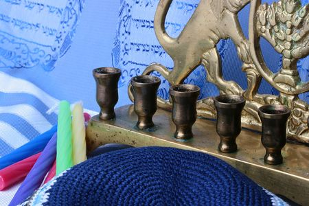 Jewish menorah and colorful candles laying on a blue and white tallit. photo