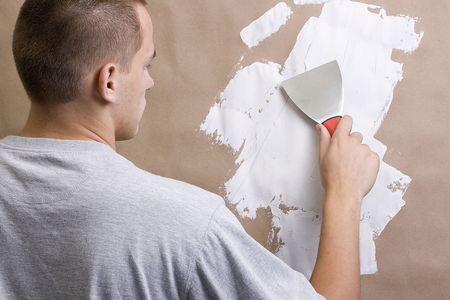 Caucasian man plastering a brown wall with a pallet. Stock fotó