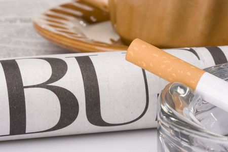 A filtered cigarette resting on a glass ashtray next to a brown cup and plate and a newspaper. Stock Photo