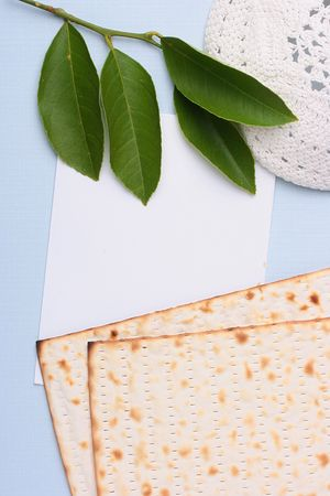 yarmulke: A white kippah and matzah next to a piece of white paper. Add your text to the paper.