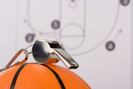A silver whistle laying on an orange basketball in front of a diagram of the game plan. photo