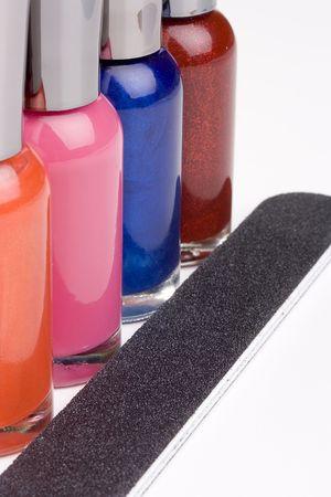 nail polish bottle: Different colored nail polish bottles next to a nail file.