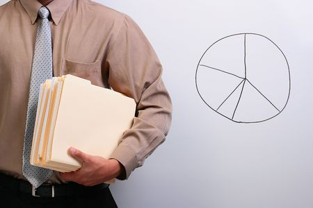 Man in a shirt and a tie holding manila folders while standing next to a pie chart. photo