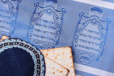 A blue kippah next to matzah and a Jewish tallit. Add your text to the background. photo