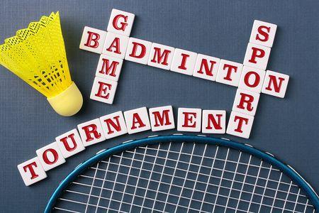 A yellow synthetic badminton shuttlecock next to a racquet and a badminton crossword. photo