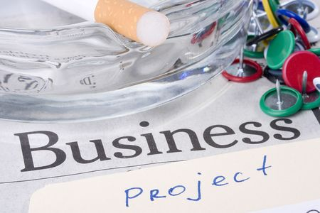 A manila project folder laying on a newspaper with the word business on it next to a glass ashtray with a filtered cigarette on it.