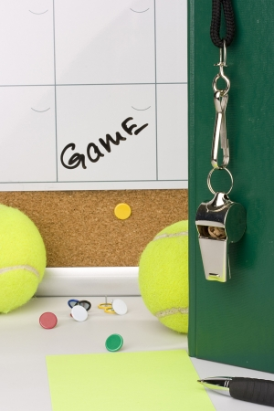playoffs: A silver whistle on a green notebook next to tennis balls and a calendar with the date of the game on it.
