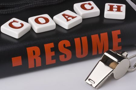 A silver whistle next to an experienced coaches resume.