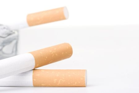 Two filtered cigarettes laying in front of a glass ashtray.