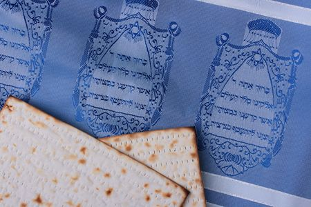 Two pieces of matzah laying on a blue tallit representing Jewish symbols.  photo