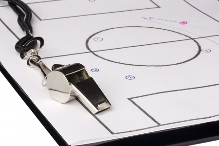 A silver whistle laying on a clipboard with the game plan on it. photo