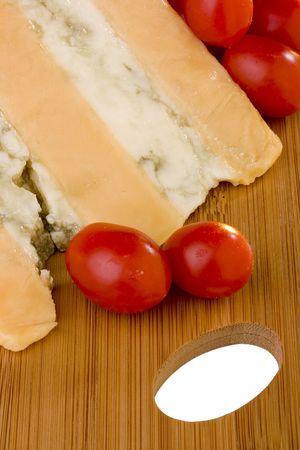グロスター チーズ チーズ青スライス トマトと木製の机の上で。 写真素材