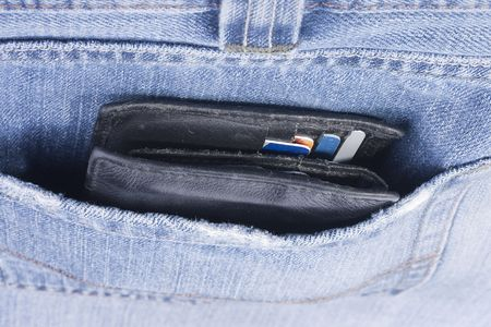 Purse with credit cards in a pocket of jeans.