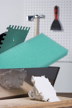 Piece of plaster laying next to plastering tools.