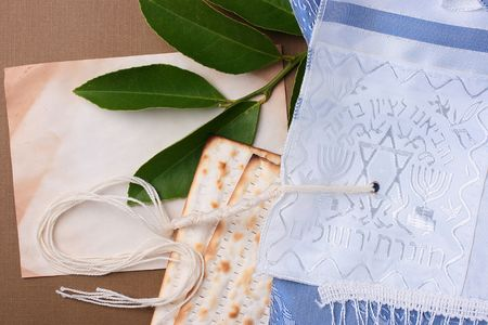 Matzah and a blue and white tallit laying next to an old piece of paper. photo